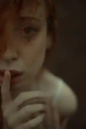 tender redhead woman with finger on lips