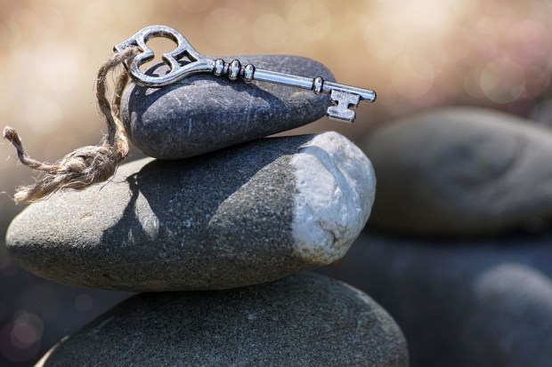 old-fashioned key sitting atop stones