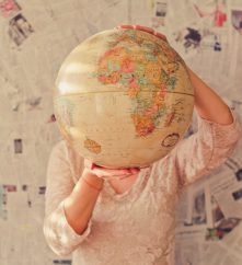 person holding a globe in front of their face