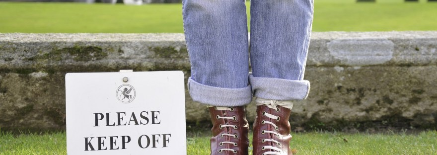"""person standing on lawn next to sign """"please keep off the grass"""""""