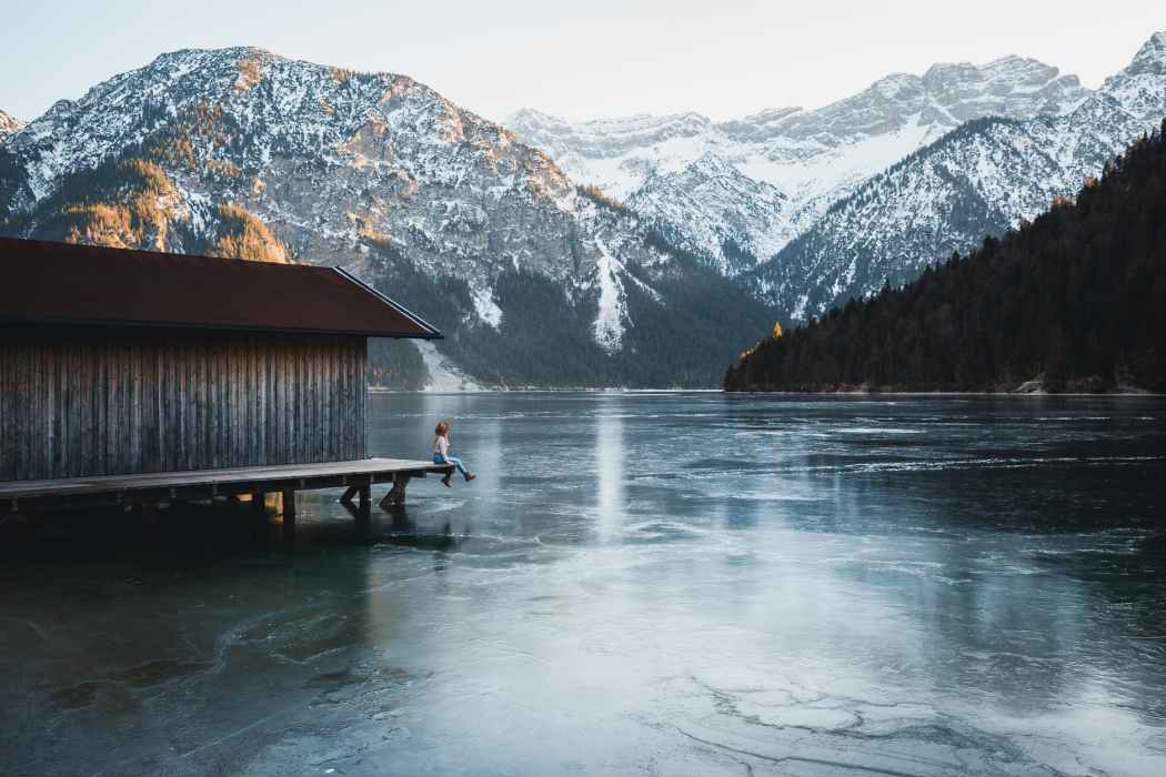 person sitting on a dock by a lake, with snowy mountains in the background
