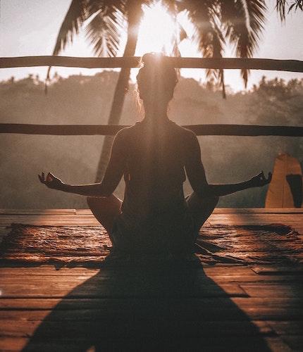 朝焼けに照らされながら瞑想をする女性