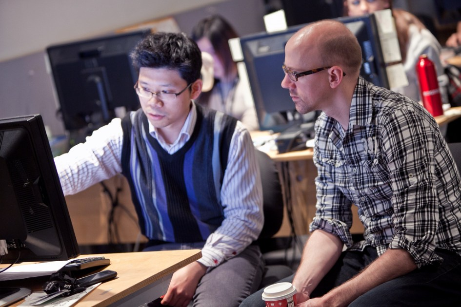 two men observing something on a computer screen