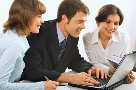 two women and one man looking at a laptop