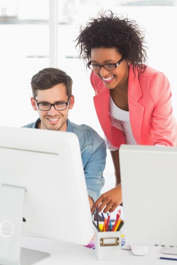 A man and woman looking at a computer.
