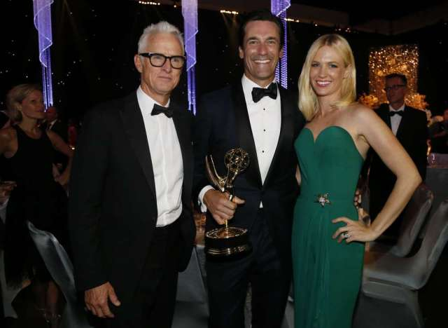 "Jon Hamm (C) holds his award for Outstanding Lead Actor in a Drama Series for his role on AMC's ""Mad Men"" while mingling with actors John Slattery and January Jones at the 67th Annual Primetime Emmy Awards Governors Ball in Los Angeles, California September 20, 2015. REUTERS/Mario Anzuoni - RTS23GW"
