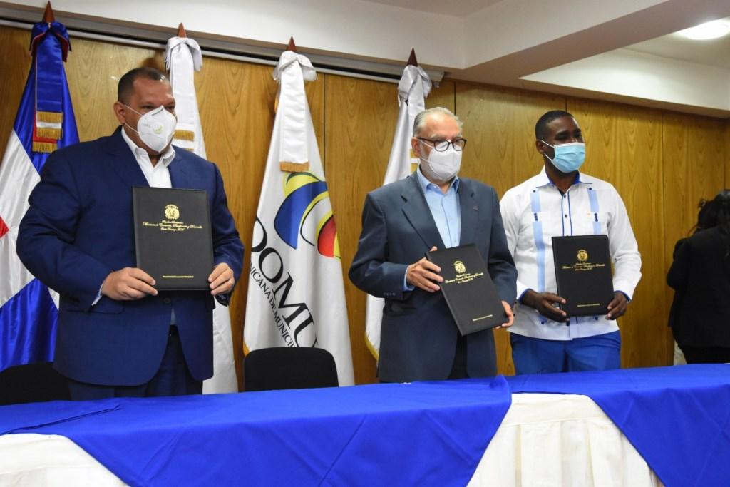 El ministro de Economía, Planificación y Desarrollo, Miguel Ceara Hatton, firma la carta compromiso con Carlos Guzmán, alcalde de Santo Domingo.