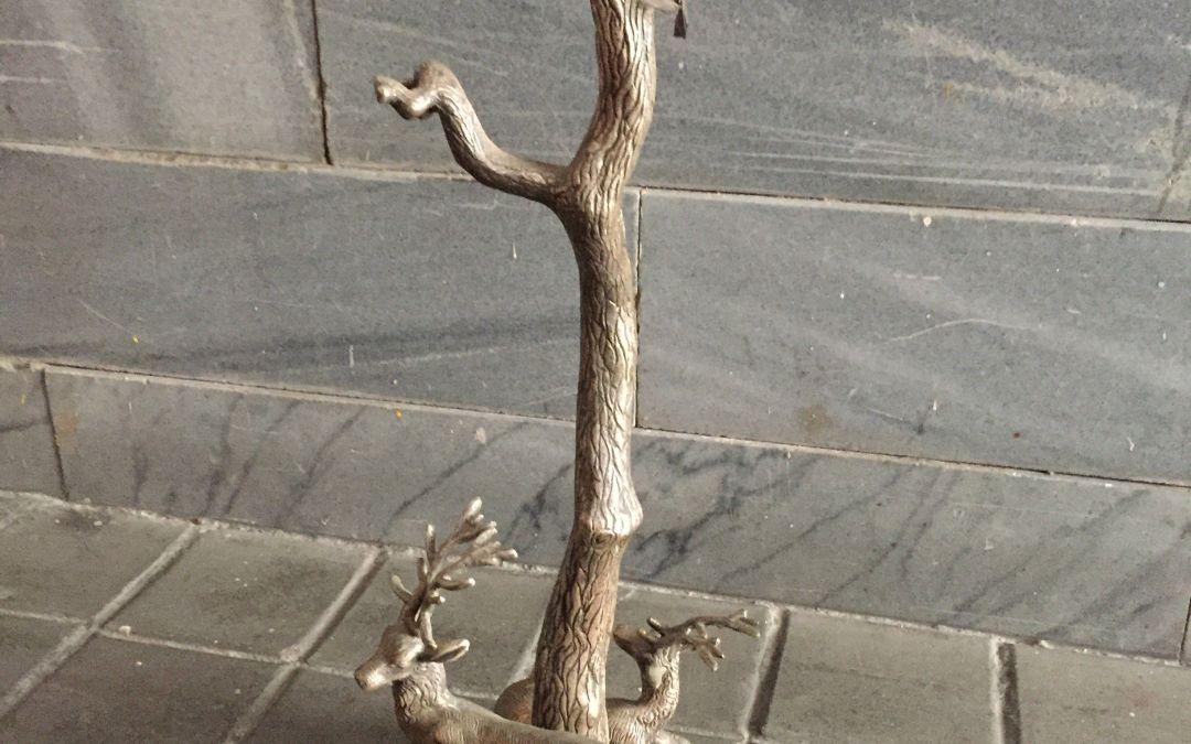 Lámpara de metal con figuras de ciervos en la base