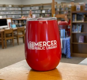 """Red insulated tumbler with clear plastic lid and """"Mercer Public Library"""" printed on the side."""