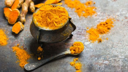 turmeric root in bowl and spoon