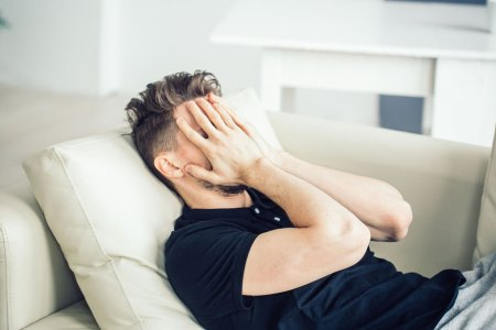 stressed male with hands over face lying on a couch