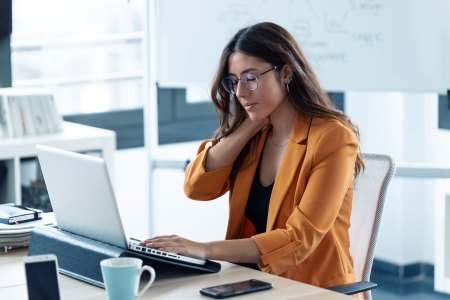 adult female experiencing neck pain while working at a computer