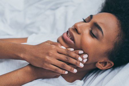 female lying in bed experiencing jaw pain