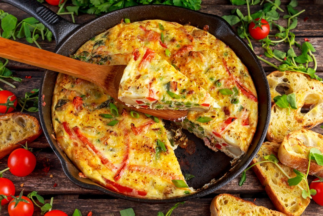 Frittata made of eggs, potato, bacon, paprika, parsley, green peas