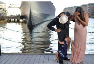 Little girl in sailor dress hugging daddys leg at maternity photo session Norfolk VA