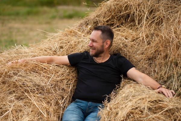 Man in black shirt sitting on hay
