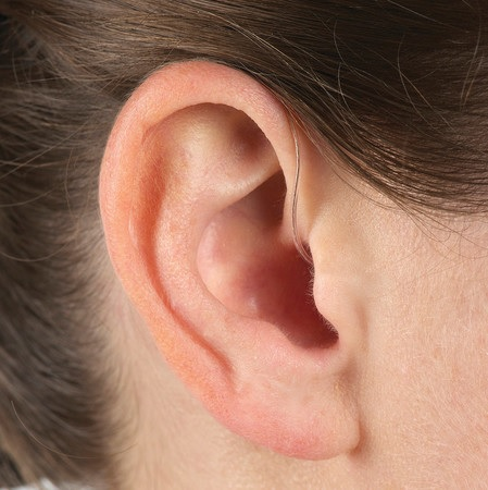close up of ear with a receiver-in-canal (RIC) hearing aid inside