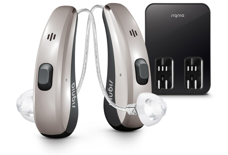 Pair of silver Signia Pure Charge & Go hearing aids standing upright shown  with black charger.