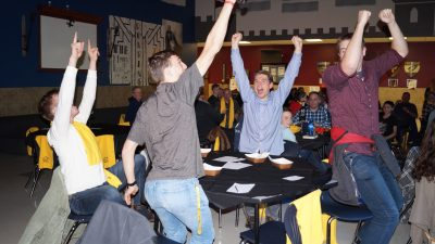 Young Adults cheering at a table