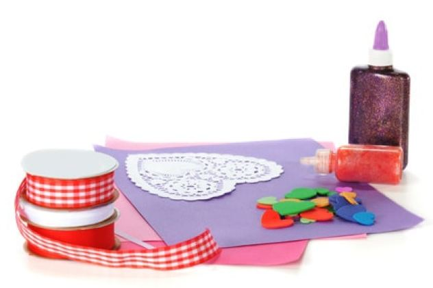 An assortment of Valentine-making supplies isolated on white.