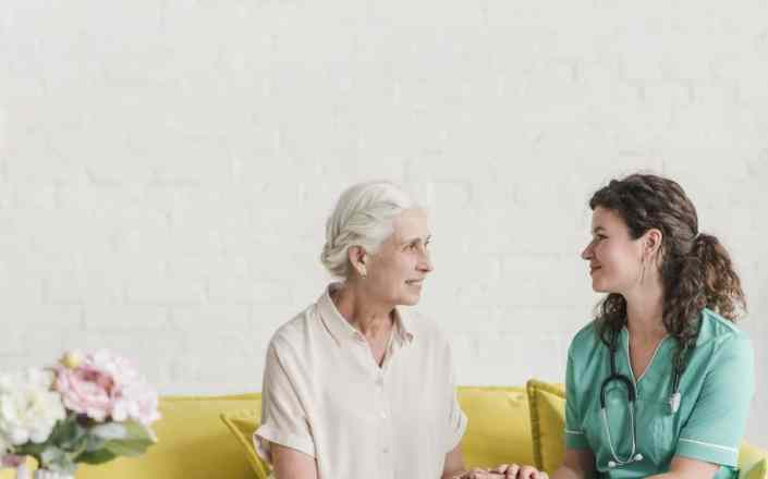 smiling-female-senior-patient-nurse-holding-each-other-s-hand