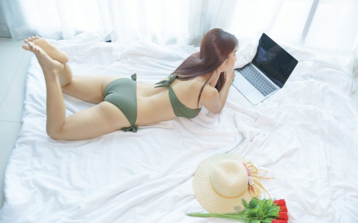 sexy-asian-woman-bikini-green-working-laptop-bed