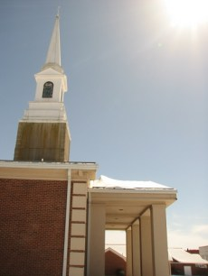 church steeple against blue sky with bright sun. Snow covers the church roof.
