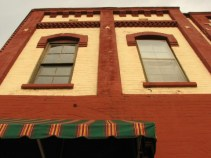 red and yellow brick building with striped canopy over door
