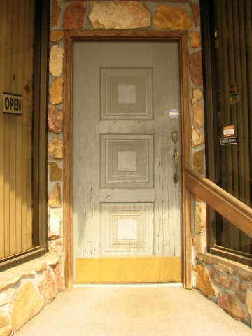 steps to gray door, rock walls and large windows on each side