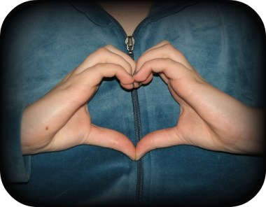 photo of hands making a heart shape, cropped with darkened edges on photo