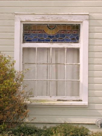 white framed window. The top section is stained glass