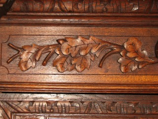 oak leaves and branches carved into a wooden hutch
