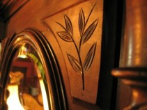 macro photo of leaves carved into a mirrored armoire