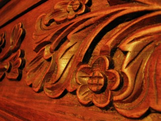 small flowers, tulips, and leaves carved into wooden furniture