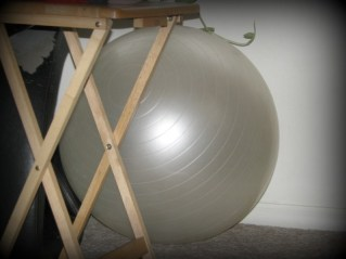 white exercise ball sitting near wall being ignored