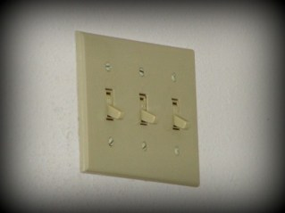 triple light switch on a white wall