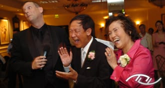 The Fun Wedding Guy, Wedding Entertainment Director® Peter Merry, eliciting laughter from the Father and Mother of the Bride at a Wedding Reception. (Photo Credit: Mike Colón Photography)