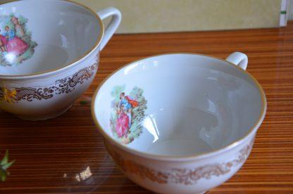 Lot de 2 tasses à chocolat Manifattura Porcellane Royal CP Trade Mark, fabriqué en Italie. Décor exterieur de volute doré et décor intérieur de couple romantique en habit 18 ème siècle.
