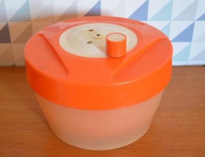essoreuse à salade orange et blanche, vintage, avec un système de frain qui permet d'arrêter de faire tourner le panier
