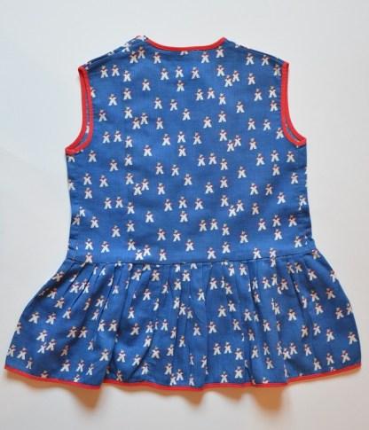 Robe d'enfant vintage bleu à décor de petits bonhommes blanc , bouton et surpiqure rouge. Elle fait 43 cm de haut, il y a 31 cm d'une aisselle à l'autre et 9 cm du cou à l'épaule. La robe ne s'ouvre pas complètement sur le devant.