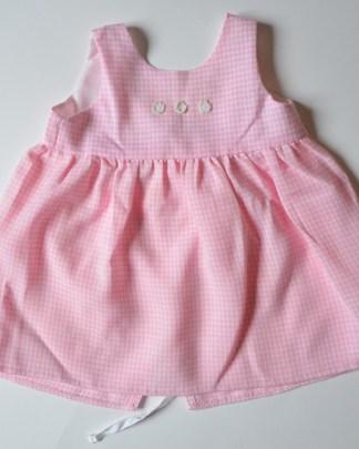 petit tablier pour bébé rose, avec des petites fleurs blanches