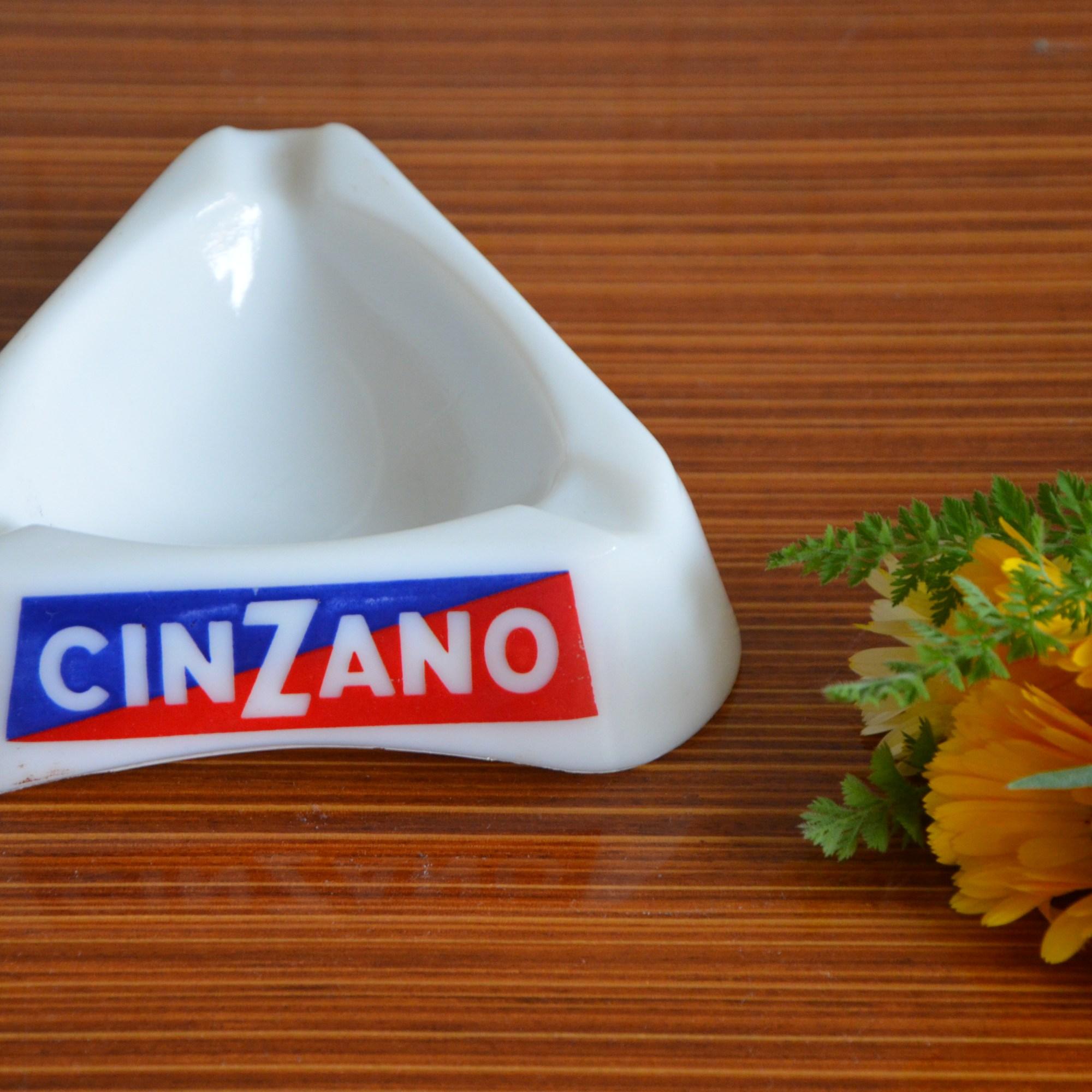 Cendrier triangulaire publicitaire Cinzano blanc avec une typographie bleu et rouge. Le cinzano est un alcool, une sorte de vermouth.