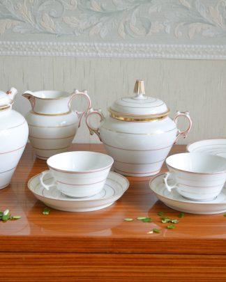 Service à thé en porcelaine très fine, avec un décor peint à la main couleur doré et ocre. Le service se compose d'une théière, d'un pot à lait, d'un pot à sucre, de 2 tasses et sous-tasses et de 2 sous-tasses supplémentaires.