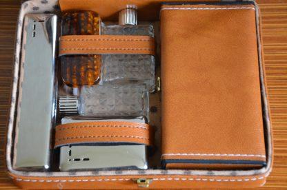 Très jolie petite valisette contenant tout le nécessaire pour partir en voyage: 2 repousses cuticules, un miroir, une boite à brosse à dent, une boite à savon, une brosse à ongles (ou à chaussures? ça me parait bien gros pour une brosse à ongles), un petit flacon et un grand flacon ainsi qu'une grande boite pour glisser tout le reste (rasoir, mouchoir, coton démaquillant, parfum etc.). Il manque juste le peigne! La boite à savon et à brosse à dents sont en plastique et le couvercle en métal très fin. Les flacon sont en verre avec des bouchons en plastique (et des petits opercules en plus pour éviter que ça fuit. Ils sont repositionnables). Le tout n'a jamais servi, sauf la boite à savon (je l'ai nettoyé, il restait du savon dedans!). Le tout fait 917 grammes.