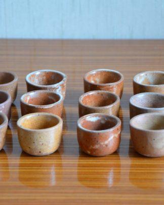 Lot de 12 coquilles à escargot en forme de pot, en grès céramique émaillée de couleur maron, rouge, jaune et piqueté de noir. Ces petits pots peuvent aussi servir à mettre des condiments sur une table. Ça sera du plus belle effet!