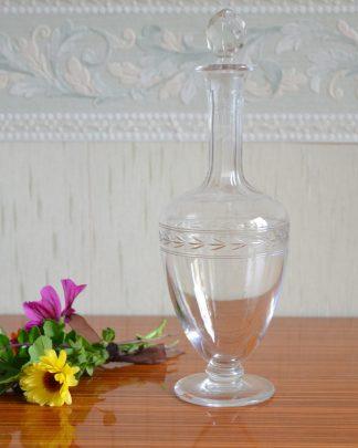 Fiole en verre sur pied gravé à la main, ciselé avec un long col. Bouchon cabochon taillé en diamant. éclat sur le pied