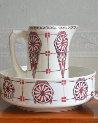 Ensemble de toilette de la manufacture Céranord St Amand Nord, en porcelaine, Made in France. Le lot est composé d'un broc, d'une cuvette de toilette d'un porte-savon et d'un bol à raser. L'anse du broc est travaillée. Motif rouge et vert Art Déco.