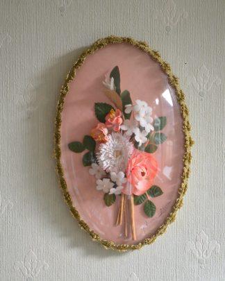 Cadre ovale, verre bombé et fleurs en plastique tour en crochet doré, fond en tissu rose, derrière en velours noir, signé Anne-Marie.