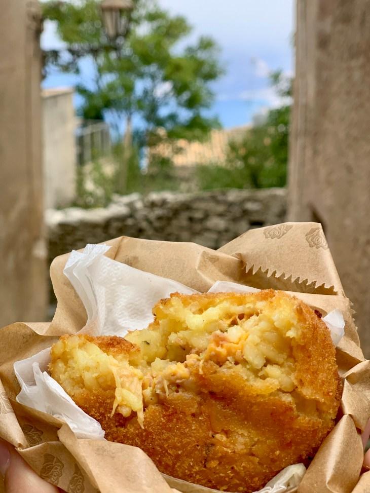 Un arancino au jambon fromage, face à une ruelle d'Erice.
