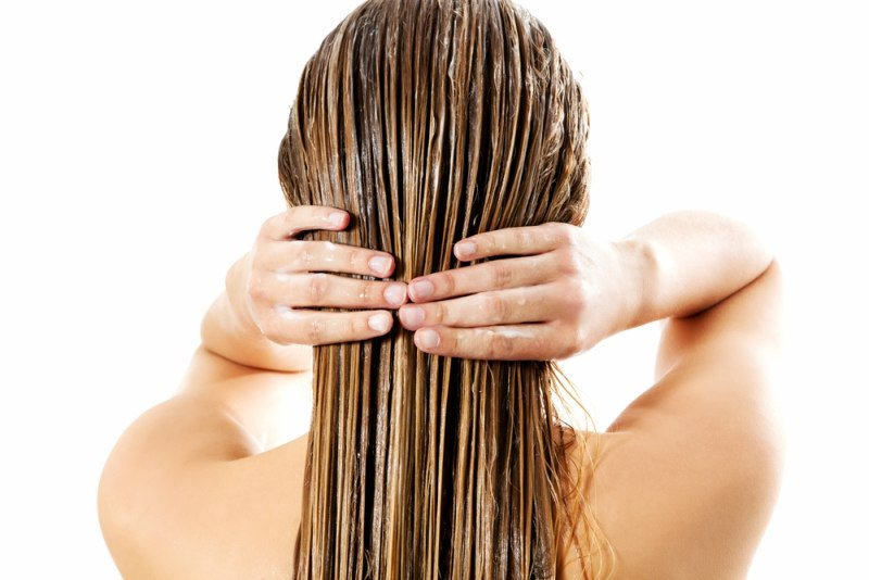 Woman-applying-hair-conditioner.-Isolated-on-white.